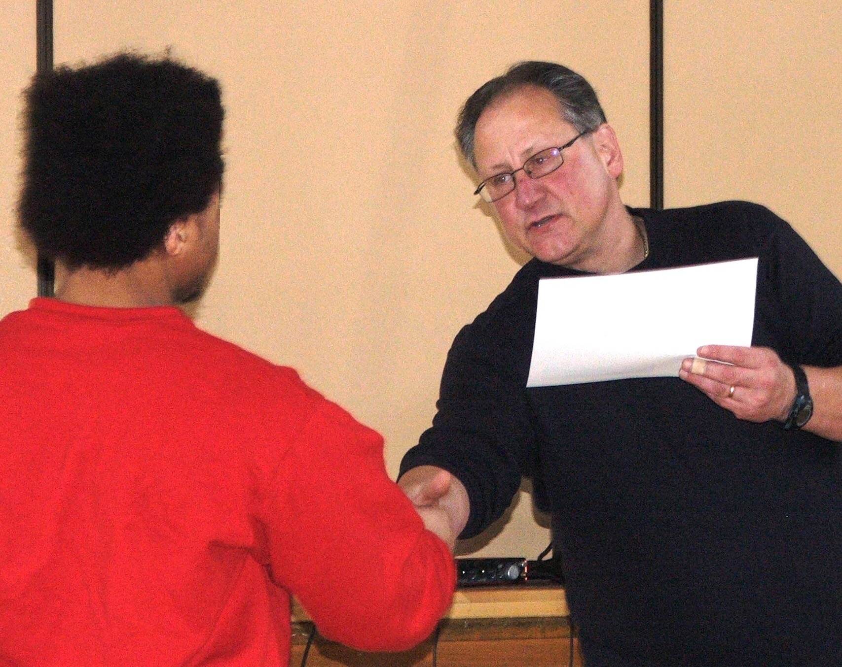 A staff member presents a diploma to a youth and shakes his hand