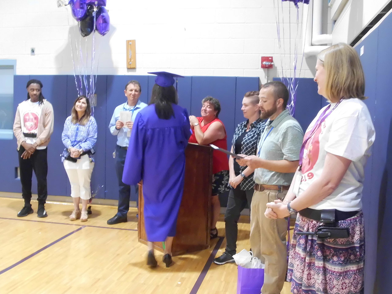 A graduate in a purple gown and mortar board accepts her diploma